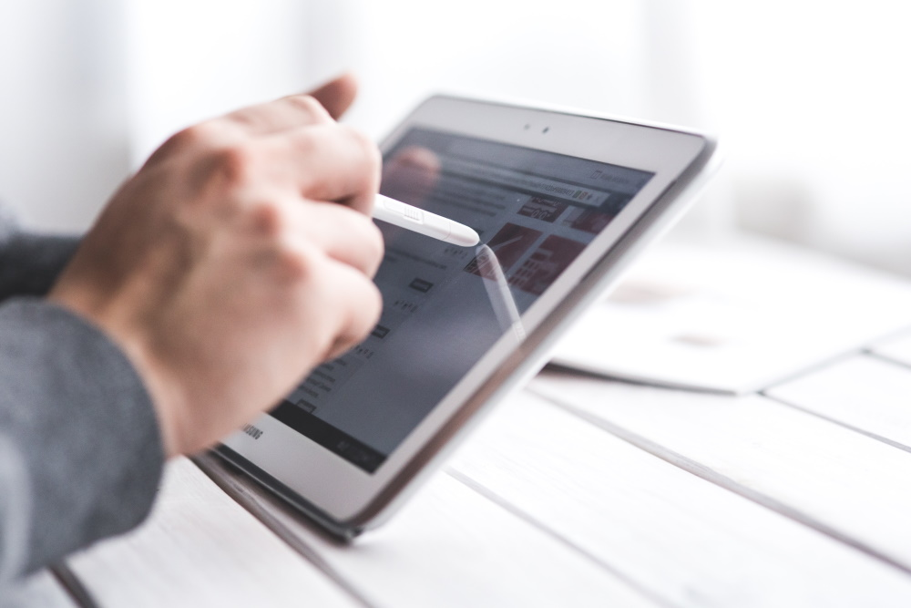 An image of a hand using a stylus to work a tablet.