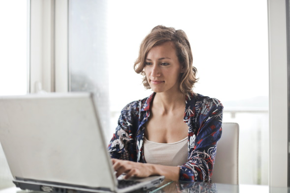 A photo of a woman sitting at a desk typing on a laptop looking down at her screen.