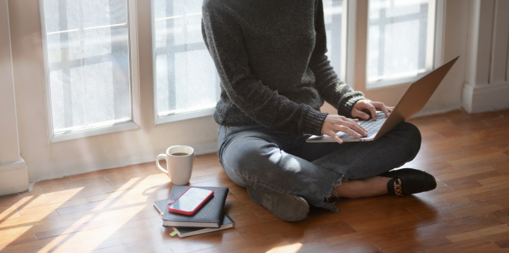 A photo of a woman sitting cross-legged on a hardwood floor typing on a laptop.