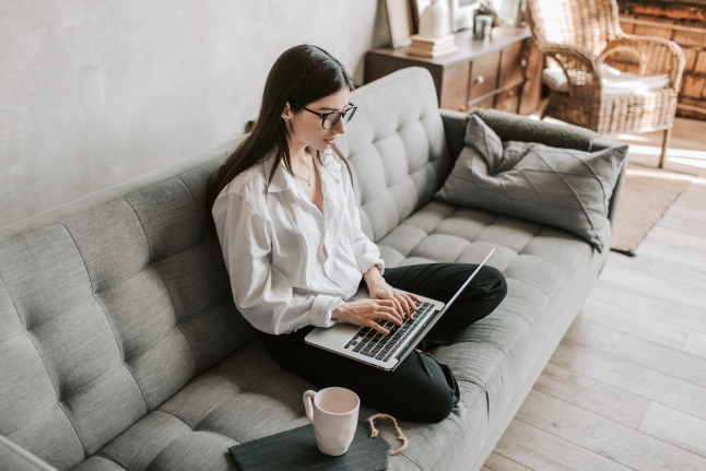 A photo of a woman sitting cross-legged on a couch typing on a laptop