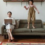 A photo of a woman working on a laptop on a couch while a little girl jumps on the couch.